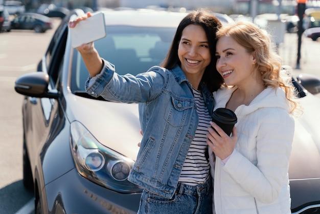Women taking a selfie next to a car