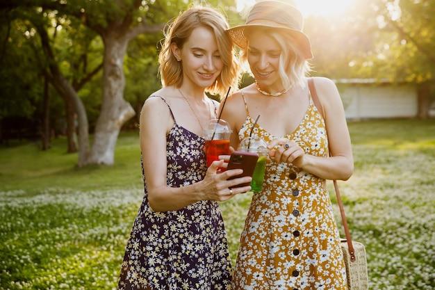 Женщины, делающие селфи, пьют коктейли в зеленом парке