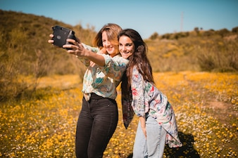 Women taking selfie in field