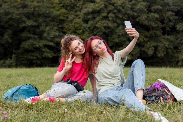 自然の中で自分撮りを取る女性