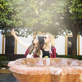 Женщины, берущие себя возле фонтана