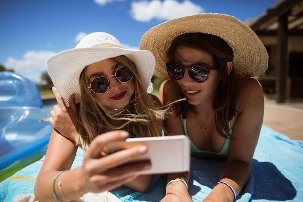 日光浴中に携帯電話で自分撮りをしている女性