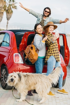Women taking selfie on smartphone near car trunk and man leaning out from auto and dog