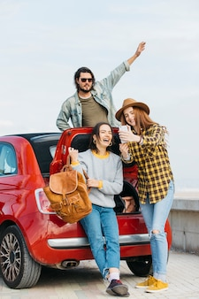 Women taking selfie on smartphone near car trunk and man leaning out from auto