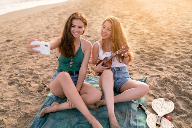 Women taking selfie while her friend playing ukulele at beach