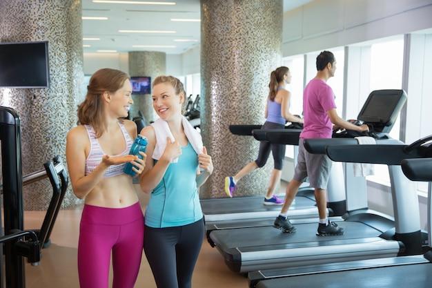 Women talking next to treadmills
