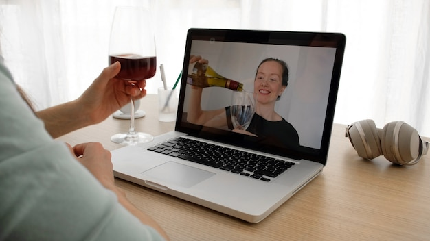 Women talking on a webcam with wine