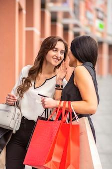 Женщины разговаривают друг с другом с бумажными пакетами