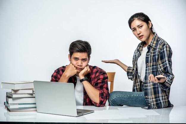 여성은 남성에게 직장에서 노트북을 사용하는 방법을 가르칩니다.