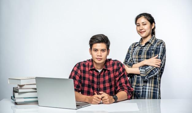 Le donne insegnano agli uomini come lavorare con i laptop al lavoro.