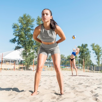 Women teammates playing volleyball on the beach