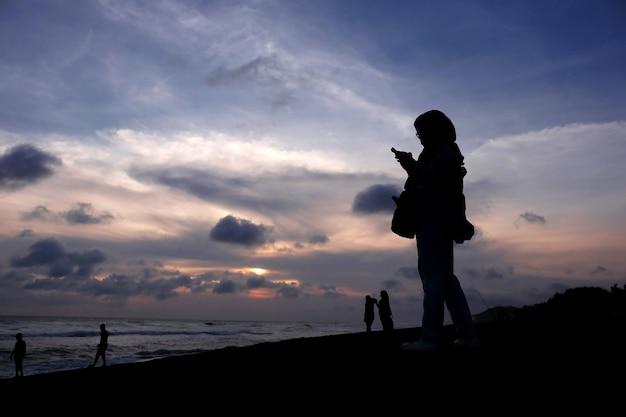 日没時にビーチでスマートフォンを使用してテキストメッセージを送信する女性