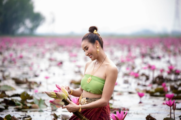 Women in thailand traditional costume standing in lotus lake