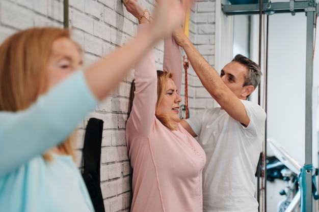 Women in their 60s and 70s doing arm exercises with a personal trainer to help with sore muscles.