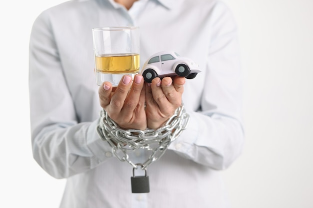 Women tied hands with chain hold glass with alcohol and toy car alcohol addiction and drunk
