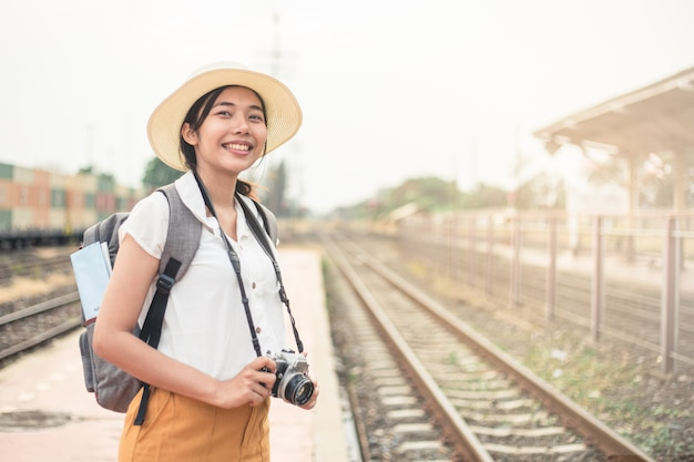 Women tourists carrying a film camera and smiling brightly at the train station