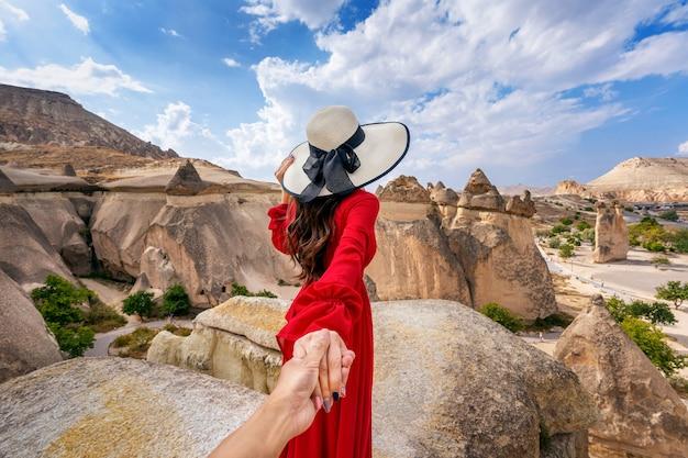 남자의 손을 잡고 그를 터키 카파도키아의 요정 굴뚝으로 인도하는 여성 관광객.