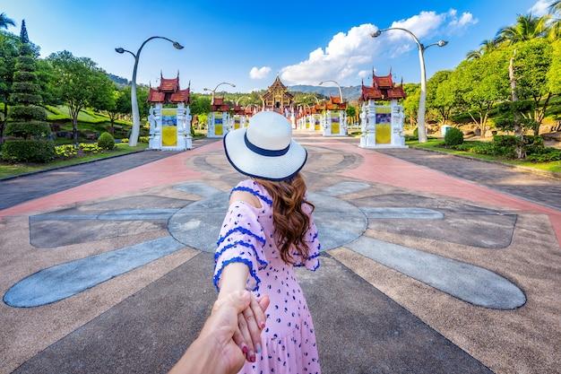 男性の手を握り、タイのチェンマイにあるロイヤルフローララチャプルークのホーカムルアン北部タイスタイルに彼を導く女性観光客。