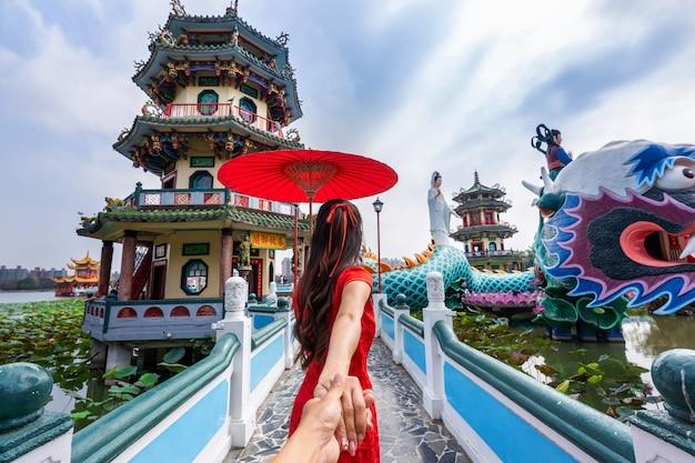 남자의 손을 잡고 그를 대만의 가오슝의 유명한 관광 명소로 인도하는 여성 관광객.