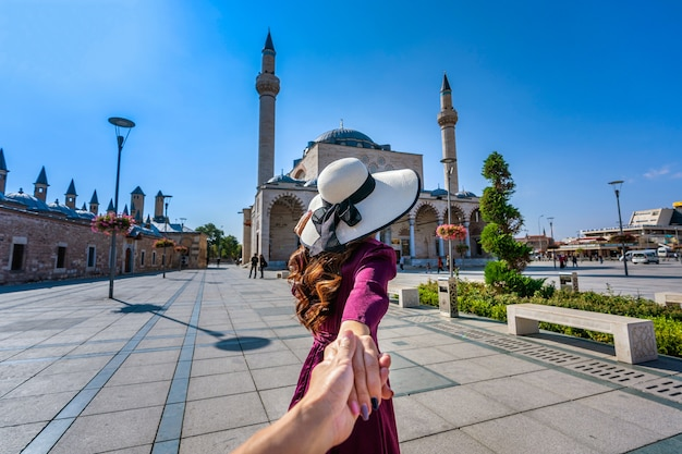 Женщины-туристы держат мужчину за руку и ведут его к мечети в конье, турция.