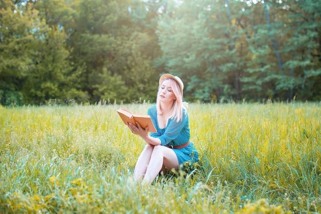 女性観光客は穏やかな自然の中で本を読みます。