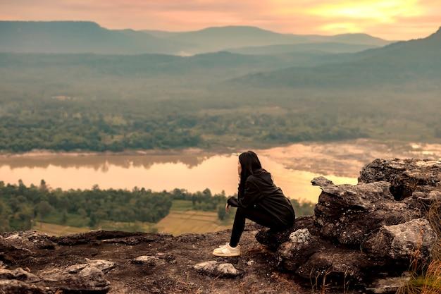 우본 라차 타니의 절벽 가장자리에 앉아있는 여성 관광객