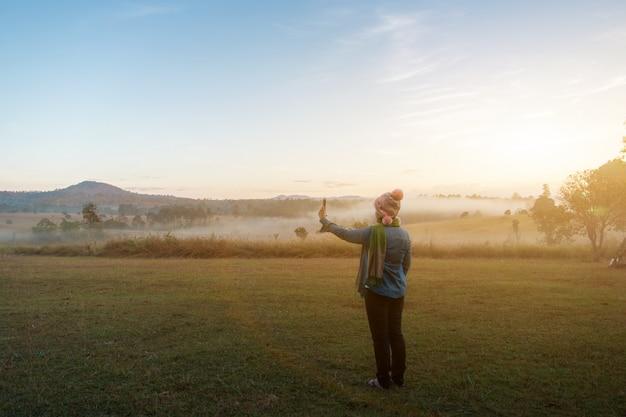 女性の観光客は夏の霧の深い朝、屋外のキャンプの冒険の概念で劇的な日の出の間にスマートフォンで写真を撮る