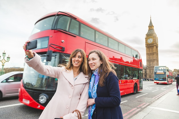 Women tourists taking a selfie at big ben in london