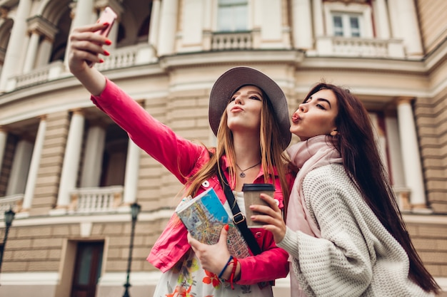 Women tourists taking selfie going sightseeing in odessa. happy friends travelers having fun