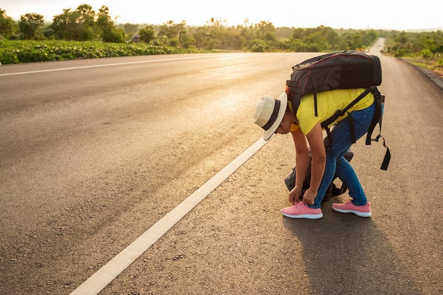 Women tourists tying the sneakers on the highway