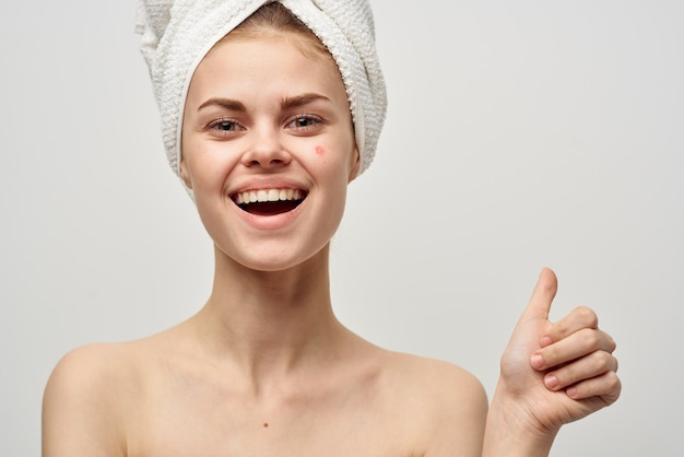 Women in a towel and with pimples on their face gesturing with their hands clean skin acne