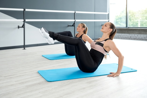 Women training abdominal muscles on mats in hall
