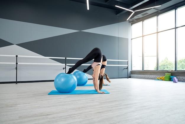 피트니스 공을 사용하여 복부 근육을 훈련하는 여성
