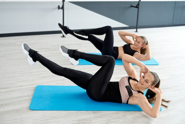 Women training abs on mats in hall