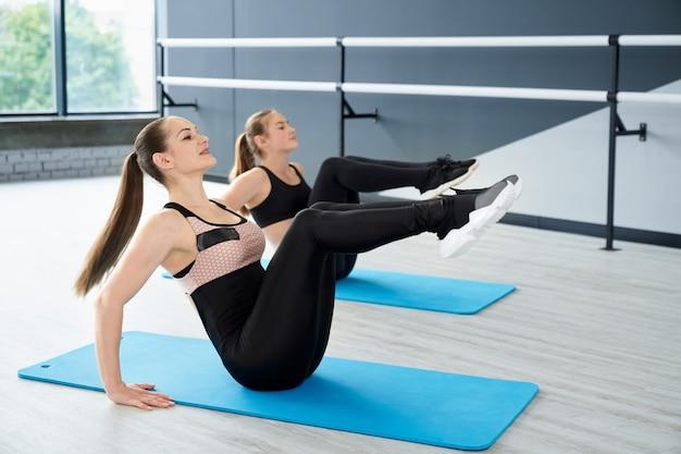 Women training core muscles on floor