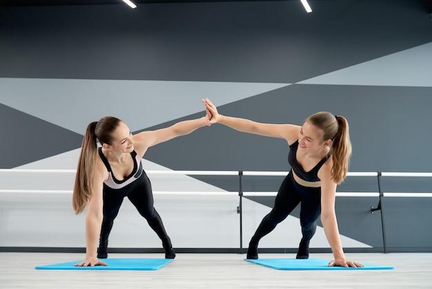 Women training on mats in dance hall