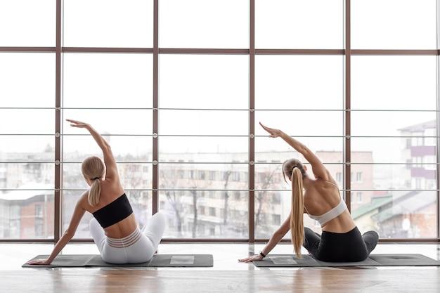 Женщины тренируются вместе на матах вид сзади