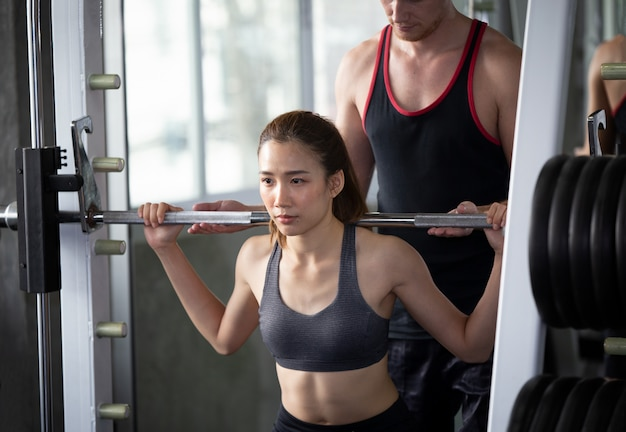 Women training weightlifting her body with trainer in fitness