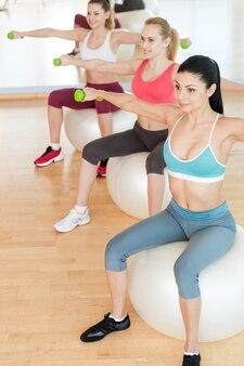 ダンベルでトレーニングする女性。スポーツウェアの3人の美しい若い女性の上面図