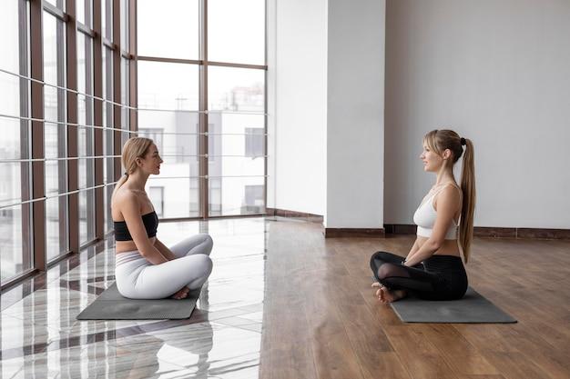 Donne che si allenano sulla stuoia di yoga pieno colpo