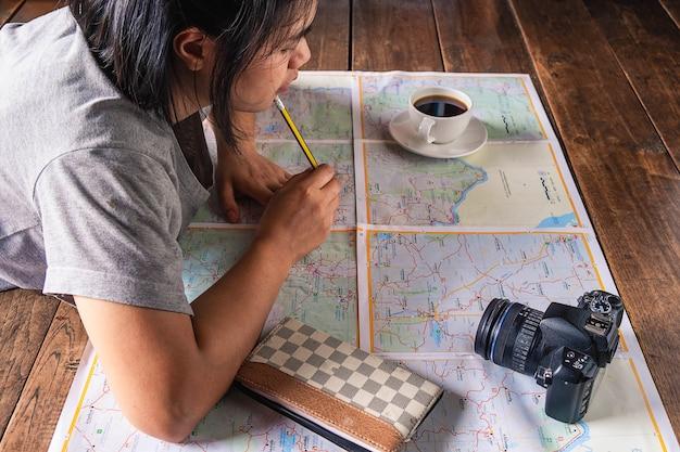 地図とカメラを使用した女性の旅行計画