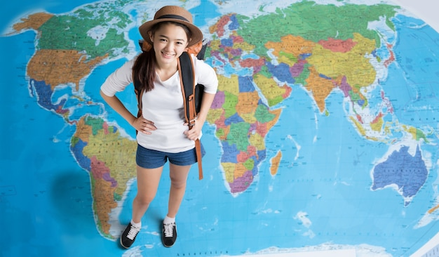 Women traveler is planning a tour of asia, her standing on the world map