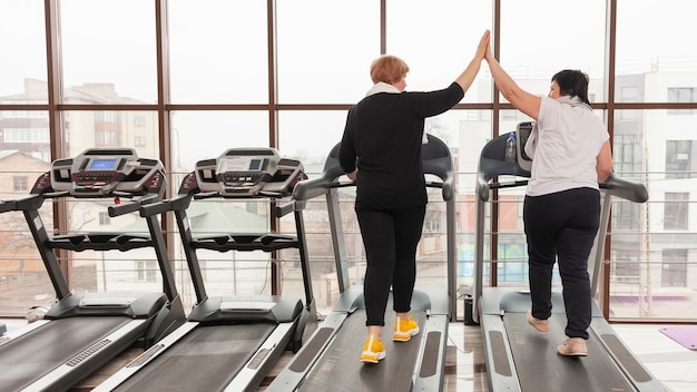 Women on treadmill high five