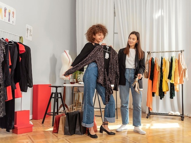 Donne che provano vestiti in negozio