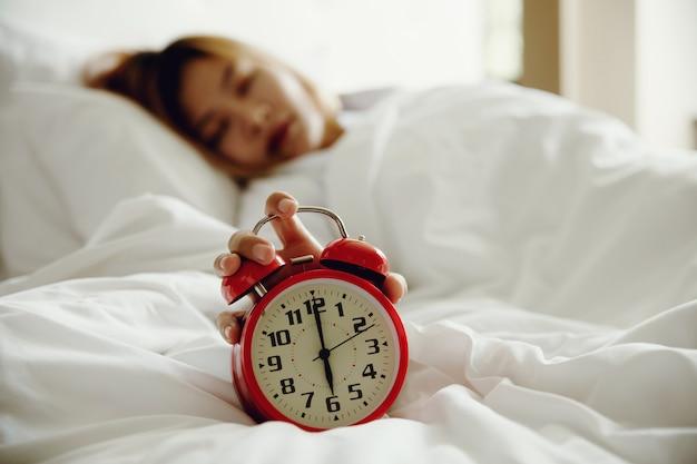 Женщины выключают будильник, просыпаясь утром от звонка