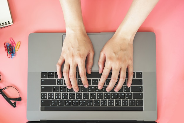 Women typing on laptop in pink pastel colourful office with accessories
