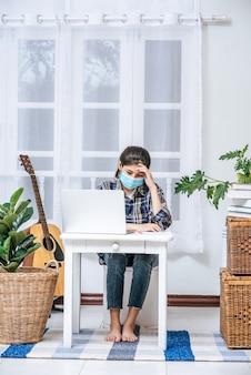女性は自分の机でラップトップを使用し、ストレスを感じています。