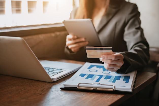 Женщины используют кредитные карты для оплаты через планшет и ноутбук при солнечном свете.