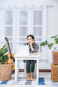 Women use a laptop at their desks and are stressed.