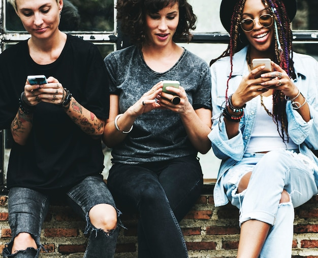 Женщины вместе пользуются мобильным телефоном